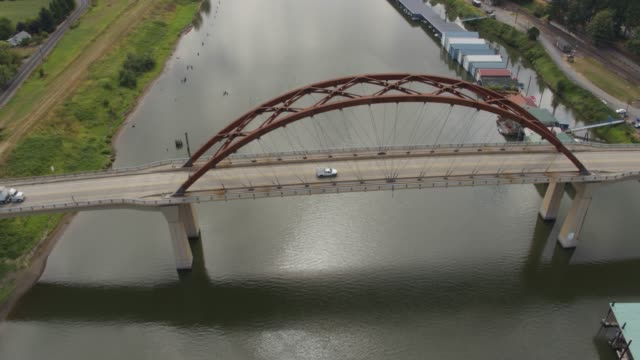 Drone aerial pull back-reveal of the Sauvie Island Bridge with house boats on each side video