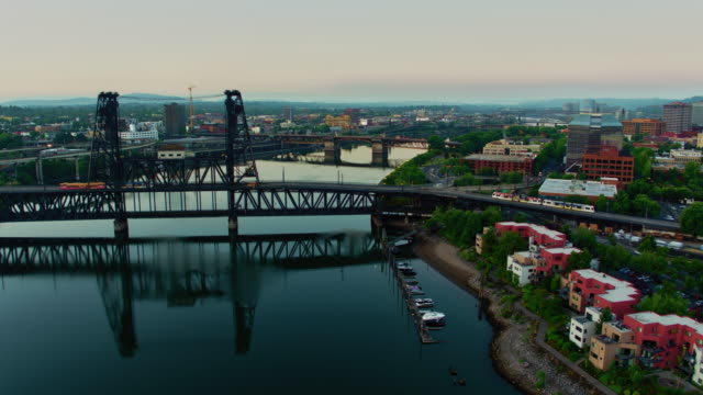 Drone aerial reveal of 2 trolleys crossing the Steel Bridge with reflections in the Willamette Rover and a flyover of Broadway Bridge and downtown Portland at sunrise on a calm summer video