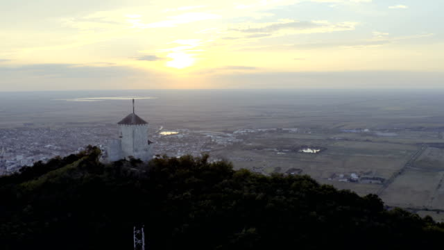 Drone aerial shot of a beautiful sunset and a tower on top of a hill