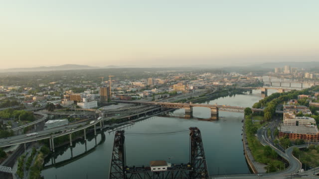 Drone aerial sunrise of the Steel Bridge with a trolley and 2 buses crossing it and 4 other bridges in downtown Portland on a summer morning video