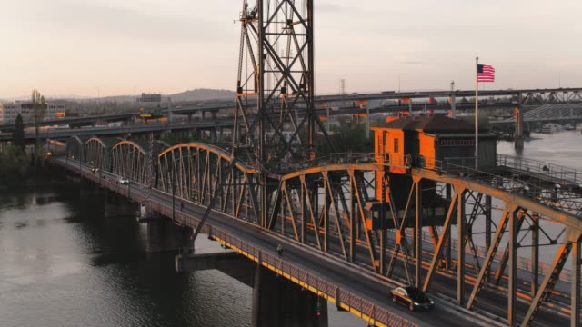 Drone aerial tracking style view of the Hawthorne Bridge with a bus crossing at sunrise in Portland Oregon video