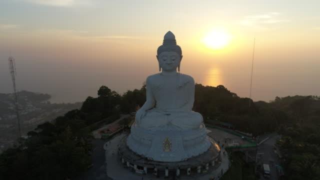 vídeos de stock, filmes e b-roll de drone vista aérea de big buda é marco ao pôr do sol em phuket tailândia - buda