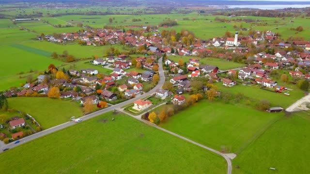 drone aerial view of small town with road farm small village in country side germany - wieś filmów i materiałów b-roll