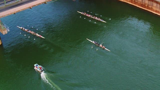 Drone Aerial view of sweep Rowing boats passing under the bridge while traffic and cyclists and runners pass over it video