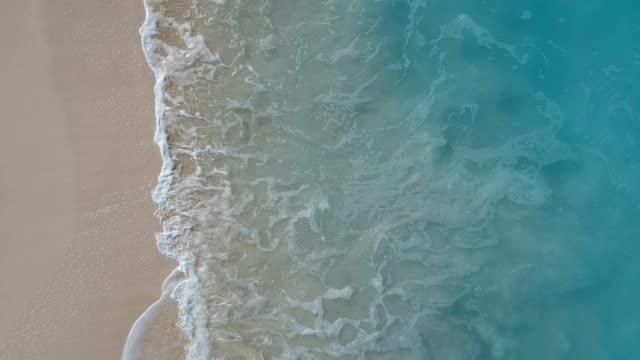 stockvideo's en b-roll-footage met luchtfoto van het gedreun van de golven op het strand in de baai van grace, providenciales, turks- en caicoseilanden - turks en caicoseilanden