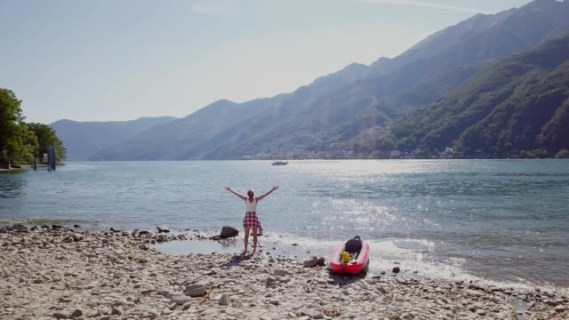 vídeos de stock e filmes b-roll de drone aerial view of young woman standing on the lakeshore near red canoe arms outstretched fro freedom and positive energy. shot n summer days in switzerland, mountains on background - lago maggiore