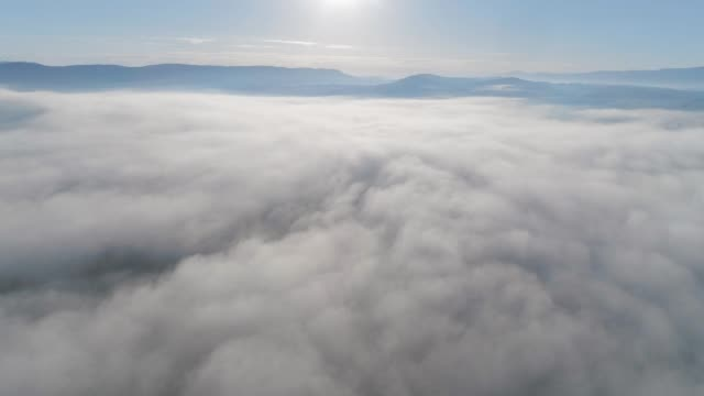 Drone: Aerial view over low clouds, sea of clouds, mist and fog over the hills, sky point of view, bright sunny day