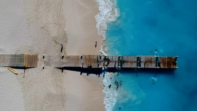 stockvideo's en b-roll-footage met drone oplopende antenne van pier in grace bay, providenciales, turks- en caicoseilanden - grace bay