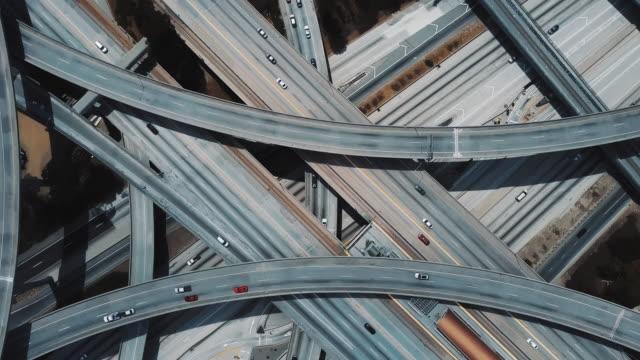 drone, steigend und spinnen schnell über große straße autobahnkreuz in los angeles mit autos auf mehrere überführungen. - aerial overview soil stock-videos und b-roll-filmmaterial