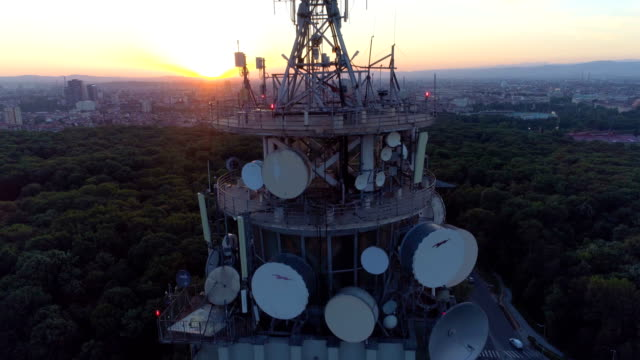 Drone ascending near radio tower at sunset revealing beautiful cityscape