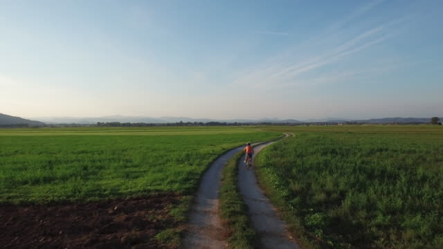 UHD Drone: Boy riding a bicycle at sunset video