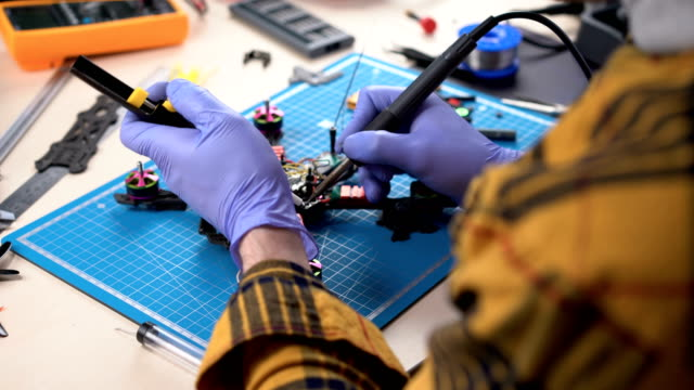 drone building, person using soldering iron to repair drone, hobby, electronics - quadcopter filmów i materiałów b-roll