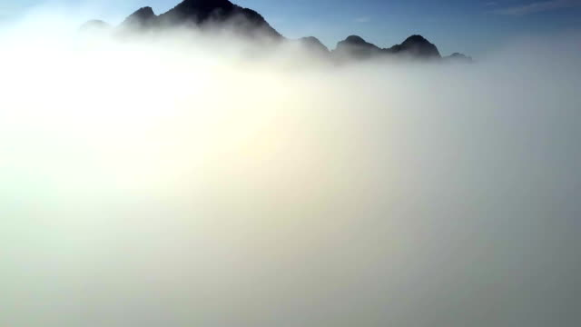 drone camera descends through thick white foggy cloud