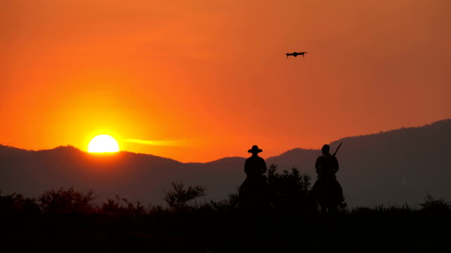 drohne kamera fliegen, um aufnahme von soldaten und cowboy reiten pferde zu fuß in den sonnenuntergang - dominanz stock-videos und b-roll-filmmaterial