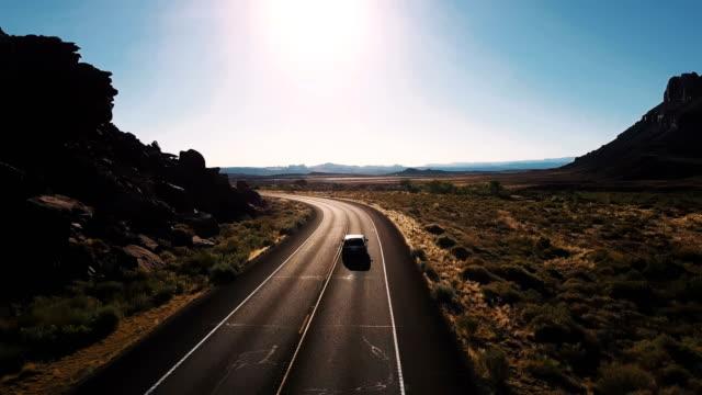 vídeos de stock, filmes e b-roll de câmera de drone segue monovolume carro virando à esquerda na estrada deserta estrada entre espaços abertos de tirar o fôlego e montanhas. - veículo terrestre