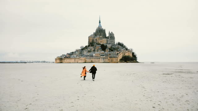 Drone camera follows young happy couple holding hands running towards epic Mont Saint Michel fortress island in France. video
