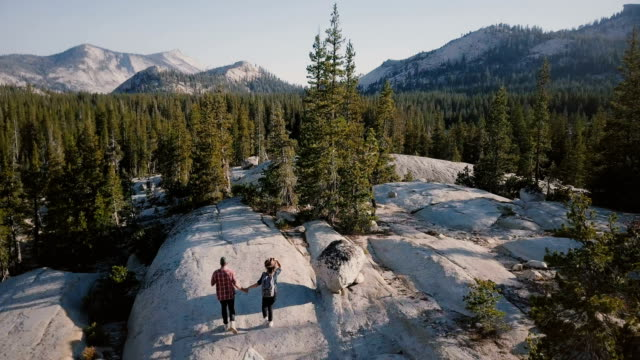 drone camera follows young happy couple run and hike together on amazing white rock towards epic yosemite park skyline. - park narodowy yosemite filmów i materiałów b-roll