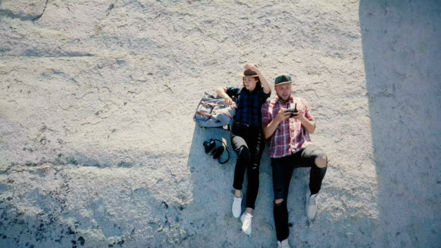 drone camera tilts down on happy romantic blogger couple with remote lying together on a rock among yosemite park forest - telecomando background video stock e b–roll
