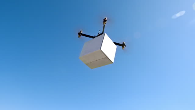 Drone carrying a box across the hills in sunshine video