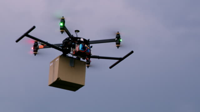 ws drone carrying a package against cloudy sky - drone stock videos & royalty-free footage