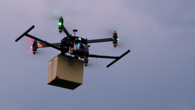 vídeos de stock e filmes b-roll de ws drone carrying a package against cloudy sky - entregar