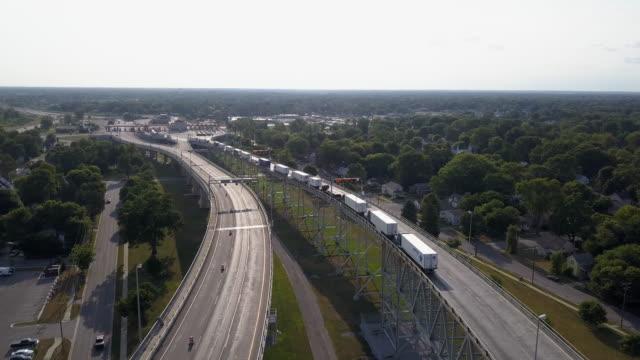 vídeos y material grabado en eventos de stock de drone clip mirando hacia abajo en una larga línea de semis alineados en el cruce fronterizo canadiense - canadá