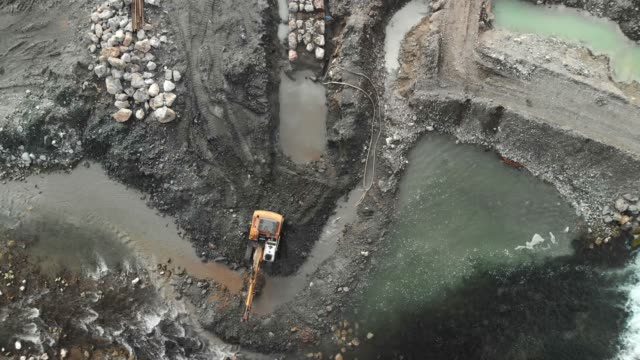 Drone close up of an excavator digging a pit in the river stream Excavator digging a pit, changing the river bed natural path. Zoom in shoot of an excavator at construction site of a dam. crane construction machinery stock videos & royalty-free footage