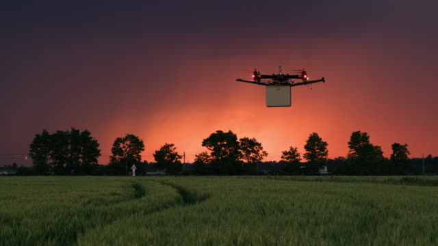 WS Drone delivering a package on a field at dusk video