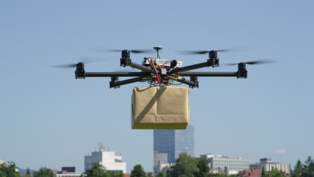 CLOSE UP: UAV drone delivery delivering big brown post package into urban city CLOSE UP: UAV drone delivery. Multicopter flying big brown package into city. Drone delivering post package to your home. Futuristic shipment by helicopter drone. Multirotor logistics and transport. robot stock videos & royalty-free footage