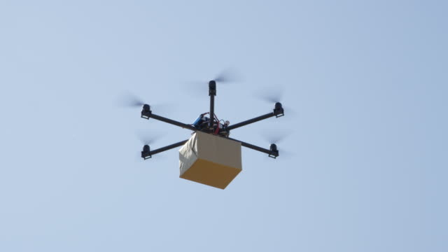 vídeos de stock e filmes b-roll de close up: drone delivery, multirotor helicopter flying big brown post package - multicóptero