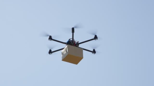 クローズ アップ: ドローン マルチロータ ラジコンヘリで茶色の大きなポスト パッケージ配信 - マルチコプター点の映像素材/bロール