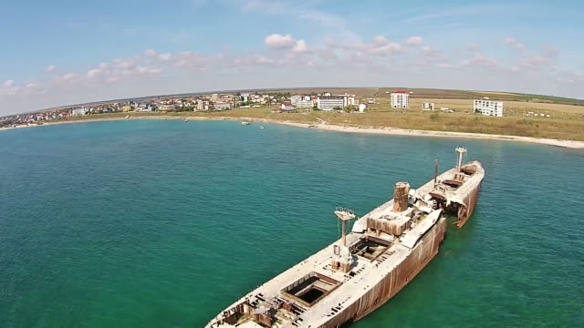 Drone descending near the shipwreck Evangelia , showing advanced structural damage of the upper deck and entire vessel  , stranded on the Black Sea coast , Romania video