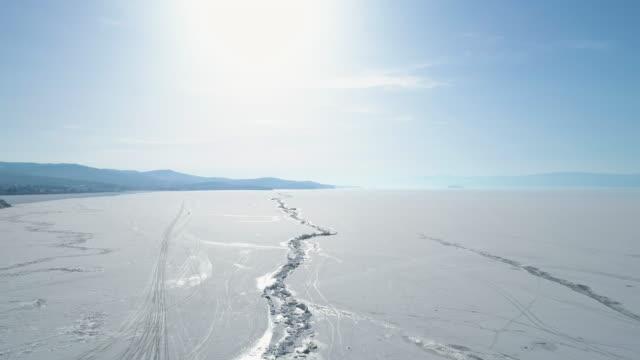 vídeos de stock e filmes b-roll de drone descends over ice crack of a frozen lake baikal - lago baikal
