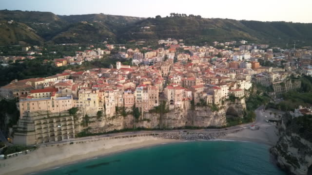 drone flies from the tyrrhenian sea to old medieval houses located on a rock - tropea video stock e b–roll
