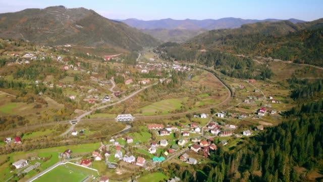 drönare flyger över en stad omgiven av berg - karpaterna tåg bildbanksvideor och videomaterial från bakom kulisserna