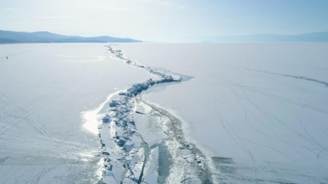 dron leci nad gigantycznym pęknięciem lodu na powierzchni zamarzniętego jeziora bajkał - antarktyda filmów i materiałów b-roll
