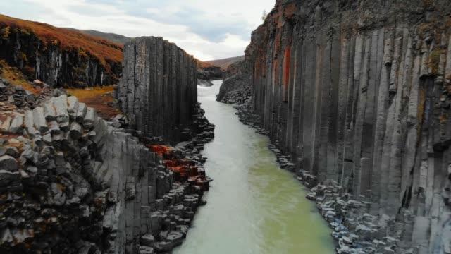 drohne fliegt über schlucht von schwarzen basaltsäulen, island - vulkan stock-videos und b-roll-filmmaterial
