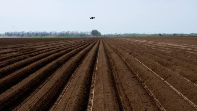ドローンはフィールドの上を飛びます。新しく耕された農業分野の長い、まっすぐな土列、毛皮のパターン。栽培機でジャガイモを植える準備。春。視点で表示 - コントロール点の映像素材/bロール