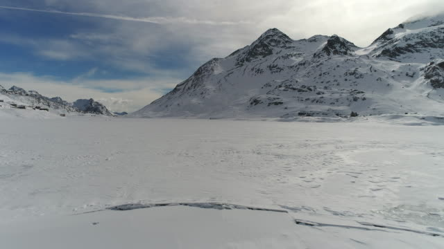 Drone flies over frozen mountain lake video