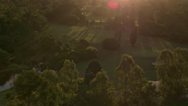 vidéos et rushes de le drone vole au-dessus du terrain de golf et du parc au coucher du soleil - golf