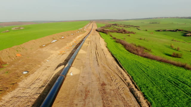 Drone flight Above Gas and Oil Pipeline. Pipes welded together, are laid on top of supportive sandbags beside the trench line. Turkish Balkanian Stream to Europe with Russian gas. gas pipe stock videos & royalty-free footage