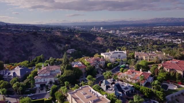 Drone Flight Across Wealthy Neighborhood Drone flight over Mulholland Estates, a gates community of luxurious homes in Sherman Oaks, California. wealth stock videos & royalty-free footage