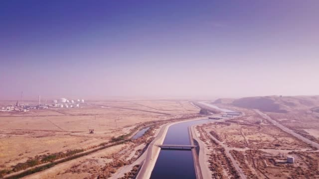 drone flight along aqueduct running through midway-sunset oil field - acquedotto video stock e b–roll
