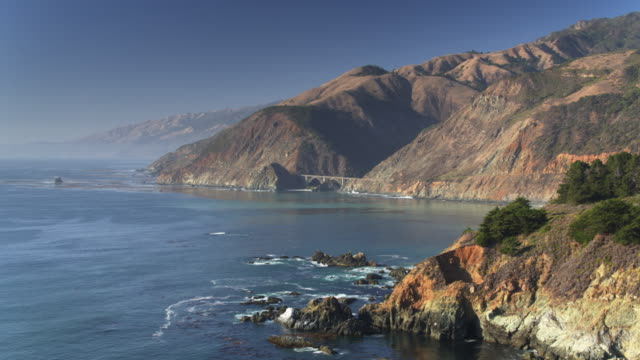 vídeos de stock e filmes b-roll de drone flight along big sur coast towards big creek bridge - montanha costeira