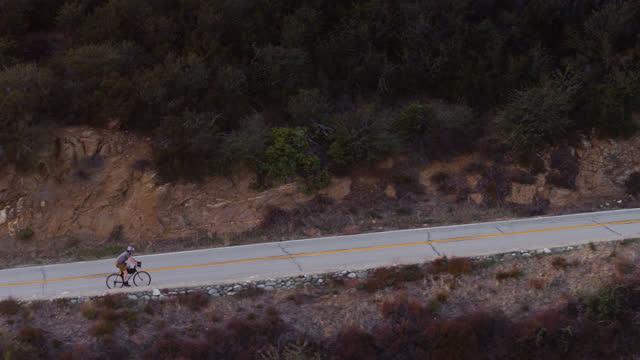 Drone Flight Alongside Cyclist Riding Up Mountain Road
