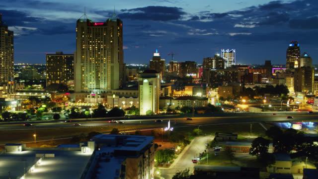 drone flight alongside freeway cutting through downtown san antonio, texas at night - san antonio texas stock videos & royalty-free footage