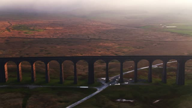Drone Flight Approaching Ribblehead Viaduct at Sunset Drone shot of the famous Ribblehead Viaduct, a 400m railway bridge made up of 24 arches that carries the Settle-Carlisle Railway across Batty Moss in North Yorkshire. Ingleborough and Whernside are covered in fog in the background. 19th century style stock videos & royalty-free footage