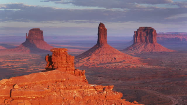 drone flight around monument valley outcrop with buttes in distance - utah video stock e b–roll