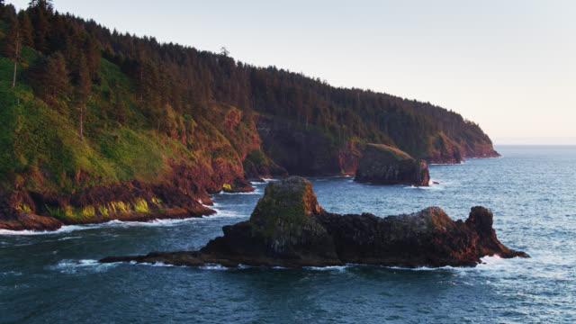vídeos de stock e filmes b-roll de drone flight around offshore rocks at cape lookout, oregon - montanha costeira