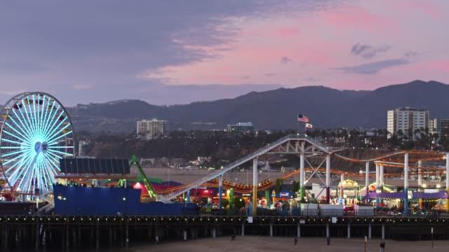 drone flight around santa monica pier at dusk - общий план перспектива стоковые видео и кадры b-roll